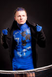 Aspiration. Man with blue bodyart painting and mozaic ornament standing  behind the net over dark background: part of bodyart project Royalty Free Stock Images