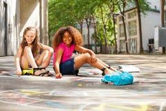 Aspiration de deux filles avec le jeu de jeu de marelle de craie dehors Images libres de droits