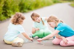 Aspiration de petites soeurs avec la craie de couleur dehors Dessins de craie Photo stock