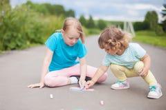 Aspiration de petites soeurs avec la craie de couleur dehors Dessins de craie Image libre de droits