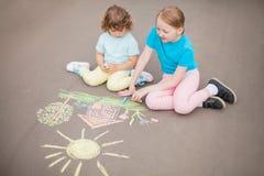 Aspiration de petites soeurs avec la craie de couleur dehors Dessins de craie Photographie stock libre de droits
