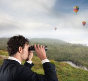 Aspiration and desire to succeed in business. Businessman leaning on a rock watching hot-air balloons in the sky with binoculars Stock Images
