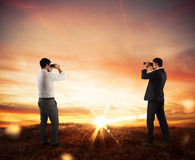 Aspiration and desire to succeed in business. Businessmen leaning on a mountain watching sunset panorama with binoculars Royalty Free Stock Photos
