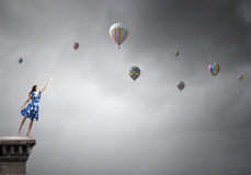 Aspiration to freedom. Young elegant woman trying to reach sky Royalty Free Stock Images