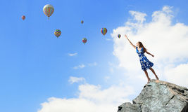 Aspiration to freedom. Young elegant woman trying to reach sky Stock Photo