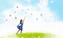 Aspiration to freedom. Young elegant woman trying to reach sky Stock Images