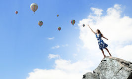 Aspiration to freedom. Young elegant woman trying to reach sky Stock Photography