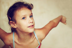 Aspirational portrait of cute kid being playful and enjoying with her arms stretched. filtered image Royalty Free Stock Images