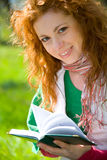Aspirations. Gorgeous red-haired girl reading notebook in summer park stock photography