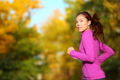 Aspirations - Aspirational woman runner running. Looking and thinking about future goals. Female athlete jogging in autumn forest in fall color foliage Stock Images