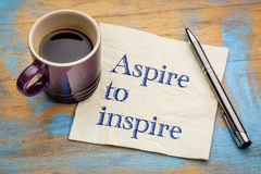 Aspire to inspire napkin note. Aspire to inspire - handwriting on a napkin with a cup of espresso coffee stock image