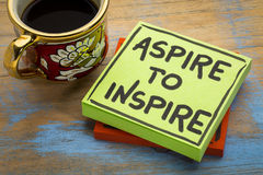 Aspire to inspire reminder or advice. Handwriting in black ink on a sticky note with a cup of coffee royalty free stock image