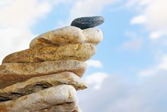 Aspire in top. Black stone on top of a pile against the summer sky Royalty Free Stock Photo