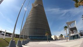 Aspire Tower Hotel. Doha, Qatar - February 21, 2019: Aspire Tower or The Torch Doha, skyscraper hotel in the sky with palm trees in the Aspire Park located in stock video