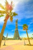 Aspire Tower Hotel. Doha, Qatar - February 21, 2019: Aspire Tower or The Torch Doha, skyscraper hotel in the sky with palm trees in the Aspire Park located in stock images