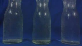 Aspirin ή ζωηρή μείωση χαπιών σε ένα ποτήρι του νερού στο μπλε υπόβαθρο φιλμ μικρού μήκους