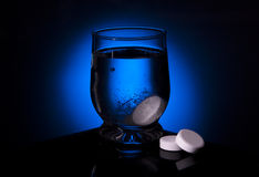 Aspirin glass water blue tablet Royalty Free Stock Photos