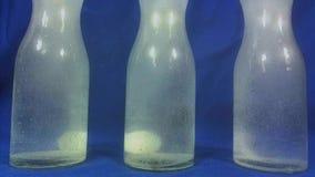 Aspirin o pillola effervescente che cade in un bicchiere d'acqua su fondo blu archivi video