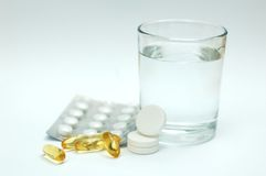 Aspirin/paracetamol and a glass of water. Aspirin/paracetamol/colored pills and a glass of water Stock Image