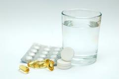 Aspirin/Paracetamol und ein Glas Wasser Stockbild