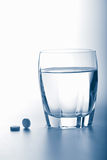 Aspirin pills and glass of water. Toned blue Royalty Free Stock Photo