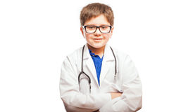 Aspiring little doctor smiling. Happy kid aspiring to become a doctor and dressing up like one with a lab coat and stethoscope royalty free stock image