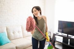 Aspiring musician assuming mop as mike singing. Playful woman singing with mop mike while cleaning house Stock Photos