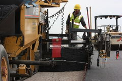 Asplant paving worker. Paving airport with asphalt paving machine Royalty Free Stock Images