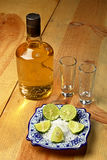 ASPTequila2.jpg. Tequila bottle and stuff on a wood table Stock Photos