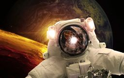 Asrtonaut in deep space near earthlike planet . Elements of this image furnished by NASA royalty free illustration