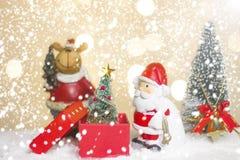 Ass.Comm. ed albero miniatura di Santa di Natale su neve sopra il fondo vago del bokeh, l'immagine della decorazione per la festa immagine stock libera da diritti