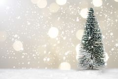 Ass.Comm. ed albero miniatura di Santa di Natale su neve sopra il fondo vago del bokeh, l'immagine della decorazione per la festa immagini stock
