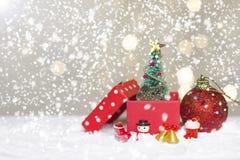 Ass.Comm. ed albero miniatura di Santa di Natale su neve sopra il fondo vago del bokeh, l'immagine della decorazione per la festa fotografie stock libere da diritti