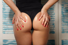 Ass in oil, a girl in a black swimsuit Stock Image