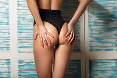 Ass in oil, a girl in a black swimsuit Royalty Free Stock Images