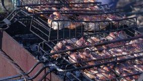 Assado com carne suculenta na grade exterior carvões e emanações quentes 4K vídeos de arquivo