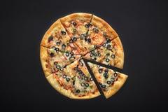 Assado da pizza com a mussarela do queijo do peperoni das azeitonas do cornichoni no fundo de pedra preto imagens de stock royalty free