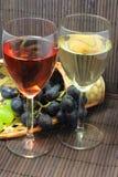 Assaggio dell'uva e della bottiglia di vino rosso e bianco Fotografia Stock