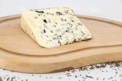 Assaggio rustico del formaggio blu con il latte della pecora su un piatto di legno immagini stock