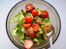 Assaisonnement pour la salade végétale, ajoutant la moutarde française à la salade végétale, nourriture de Vigatarian, nourriture images libres de droits