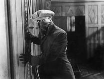 Assaltante com máscara em uma casa (todas as pessoas descritas não são umas vivas mais longo e nenhuma propriedade existe Garanti imagens de stock royalty free