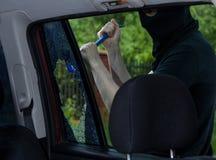Assaltante com a pé de cabra que quebra a janela de carro Fotos de Stock Royalty Free