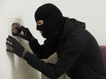 Assaltante do ladrão na quebra do código da casa imagem de stock