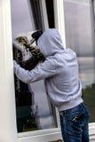 Assaltante em uma janela Fotos de Stock Royalty Free