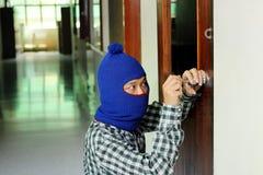 Assaltante mascarado que usa a chave falsificada através da porta antes do roubo Conceito do crime imagem de stock