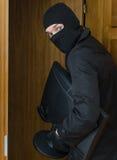 Assaltante masculino na máscara que rouba o monitor Foto de Stock
