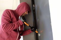 Assaltante que tenta forçar uma fechadura da porta foto de stock
