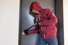 Assaltante que tenta forçar uma fechadura da porta imagem de stock royalty free