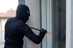 Assaltante que tenta forçar uma fechadura da porta usando a pé de cabra imagens de stock royalty free
