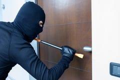 Assaltante que tenta forçar uma fechadura da porta usando uma pé de cabra imagens de stock